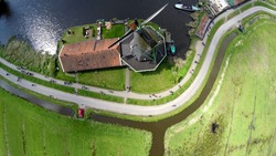 Aerial top down lower altitude view Zaanse Schans one of most popular tourist attractions of Netherlands Holland near Amsterdam drone footage looking down on windmills mills renewable energy 4k