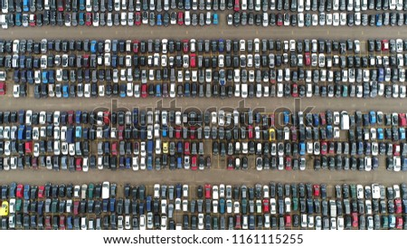 Aerial top down photo of automaker car lot showing vehicles parked close to each other ready for further distribution