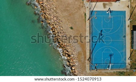Aerial top down photo of basketball court in tropical rocky island by the beach with nobody playing