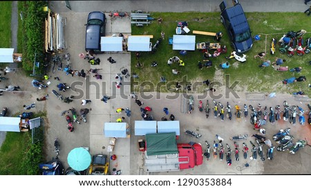 Aerial top down photo of classic motorcylce event festival terrain with old bikes and mopeds parked and visitors walking over the field also showing stalls and vintage fire truck #1290353884