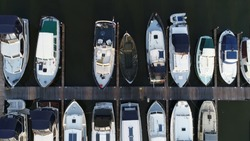 Aerial top down photo of marina a dock basin with moorings and supplies for yachts and small boats showing the floating dock walkway supported by pontoons and the recreational motor boats