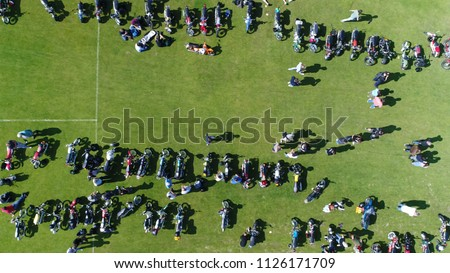 Aerial top down photo of moped event moving right over green field with the small motorcycles parked and people walking over the festival terrain steady footage during summer day