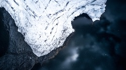 Aerial top down photo of Pastoruri glacier next to the lake with snow flakes in the air. Glacier creates abstract textures, snow is snowing, there is a light reflection in the lake's waters.