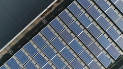 Aerial top down photo of solar panels PV modules mounted on flat roof photovoltaic solar panels absorb sunlight as a source of energy to generate electricity creating sustainable energy