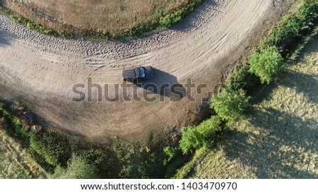 Aerial top down photo of sport utility vehicle SUV driving over off-road gravel surface advanced vehicle equipped with raised ground clearance and four-wheel drive to support countryside unpaved roads #1403470970