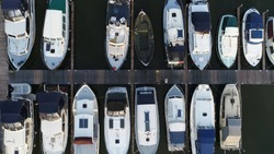 Aerial top down picture of marina a dock basin with moorings and supplies for yachts and small boats showing the floating dock walkway supported by pontoons and the recreational motor boats