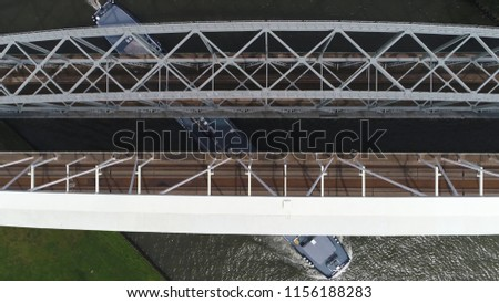 Aerial top-down picture of modern tied-arch railway bridge over canal showing barge moving underneath the large infrastructure and train moving over permanent way