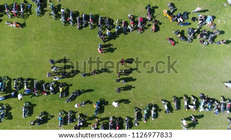 Aerial top down picture of moped event moving right over green field with the small motorcycles parked and people walking over the festival terrain steady footage during summer day