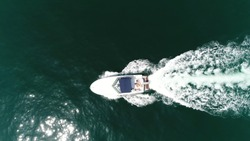 Aerial top down picture of motorboat with people sun tanning on stern side deck of boat also known as speedboat or powerboat is vessel which is powered by an engine beautiful summer day