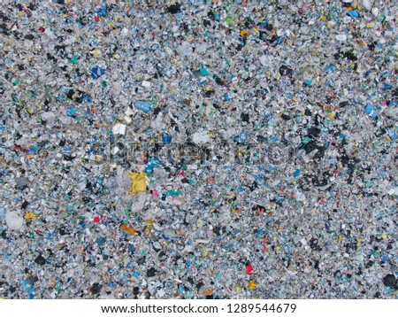 AERIAL TOP DOWN: Two dirt roads lead past large heaps of garbage in a smelly landfill. Concerning aerial view of huge piles of rubbish. Huge piles of scrap and plastic piling up in a big junkyard. #1289544679