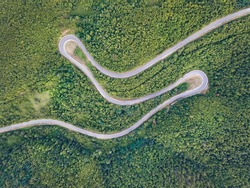 Aerial top down view drone image of curvy mountain road asphalt with serpentine through trees green forest in day summer taken in Serbia Tresibaba Knjazevac Balkans - nature travel concept