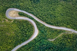 Aerial top down view drone image of curvy mountain road asphalt with serpentine trough trees green forest in day summer taken in Serbia Tresibaba Knjazevac Balkans - nature travel concept