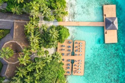 Aerial top down view from drone of a luxurious tropical island paradise resort in Maldives with wooden pier and relaxing area with chairs and tables