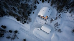 aerial top down view of a house covered in snow in the woods with cozy lights in the building