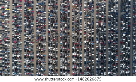 Aerial top down view of automaker distribution center with new vehicles perfectly lined up next to each other ready for further transportation retailers and dealerships