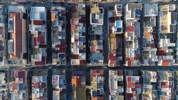 Aerial top down view of city building block located in metropolitan town flight over roofs and streets with vehicles driving around filmed by drone moving up slowly showing more of urban environment