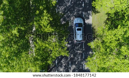 Aerial top down view of grey station wagon vehicle overtaking drone camera driving over straight road testing area for development of self driving electronic automobiles ev's 4k high resolution