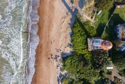 Aerial top down view of lighthouse with red top and white base. Blue sea and sand beach. Pape lighthouse