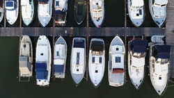 Aerial top down view of marina and docked recreational boats showing the basin with moorings for small vessels
