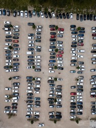 Aerial top down view of parking, many cars standing in row. Parked automobiles, trees. Parking on sand.