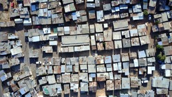 Aerial top-down view of slum medium altitude heavily populated urban informal settlement characterized by substandard housing and squalor people walking through streets and rusty metal home roof tops