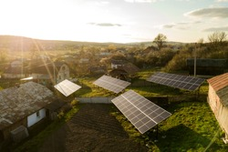 Aerial top down view of solar panels in green rural village yard.