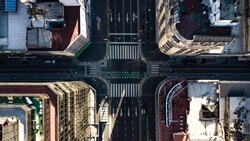 Aerial top down view on four way intersection in between tall buildings during golden hour (sunset time) with no people or traffic due to corona virus quarantine - 24 March 2020