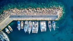 Aerial top down view over sailboats anchored in the turquoise Platis Gialos Marina on Sifnos island, Greece