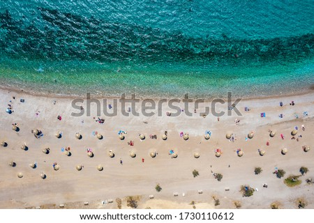Aerial top down view to the beach of Glyfada district, south Athens Riviera, Greece, with umbrellas set away from each other under Corona social distancing measures
