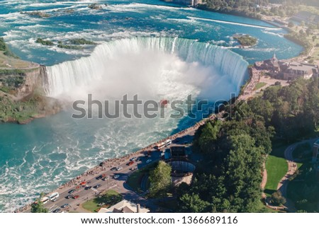 Aerial top landscape view of Niagara Falls  between United States of America and Canada. Horseshoe of Canadian waterfall on sunny day. Water tour boat at famous tourist landmark