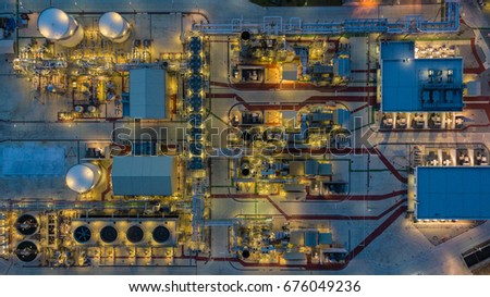 Aerial top view Electrical power plant at night, support oil refinery and gas refinery plant form industry zone.
