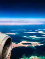 Aerial top view from airplane. coastline Egyptian  islands. Red sea Sharm Al Sheikh Egypt. Amazing shoot bird eye plane window mountains. Travel concept. turbine aircraft engine flying over ocean
