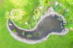 Aerial top view garden pond. Garden fish pond. Pond on natural landscape. Water garden natural pool. Exterior of a private garden. Pool with rocks
