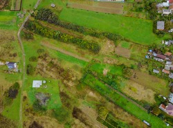 Aerial top view of a land with down green fields in countryside with grown plants row pattern