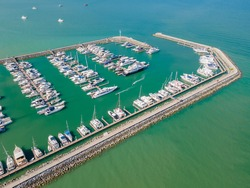 Aerial top view of a lot of white yachts and sailboats moored in marina on a turquoise water, hundreds of boats in port, Pattaya, Chonburi