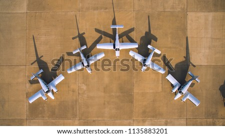 Aerial top view of a symmetry parked light aircrafts at a small countryside airfiled. Cessna and Piper