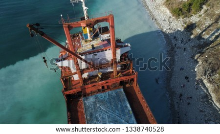 Aerial top view of an empty, red barge moored near the beautiful blue sea shore. Big Industrial ship standing near the hill with green trees.
