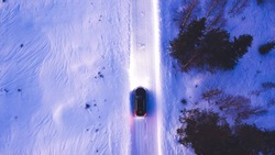 Aerial top view of black car driving on winter road in rural area while headlights illuminate the path, bird's eye view of suv vehicle crossing snowy cold lands with insurance