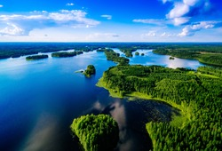 Aerial top view of blue lakes with islands and green forests in Finland. Beautiful summer landscape.