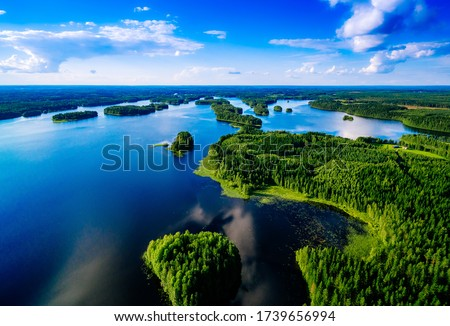 Aerial top view of blue lakes with islands and green forests in Finland. Beautiful summer landscape. Stockfoto ©