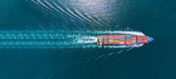 Aerial top view of cargo maritime ship with contrail in the ocean ship carrying container and running for export  concept technology freight shipping by ship smart service