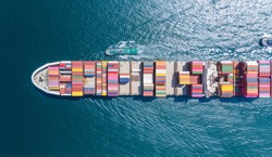 Aerial top view of cargo ship carrying container and running for export  goods  from  cargo yard port to custom ocean concept smart freight shipping maritime by ship .