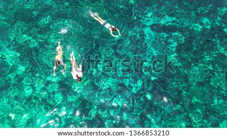 Aerial top view of family snorkeling from above, mother and kids snorkelers swimming in a clear tropical sea water with corals during summer vacation in Thailand #1366853210