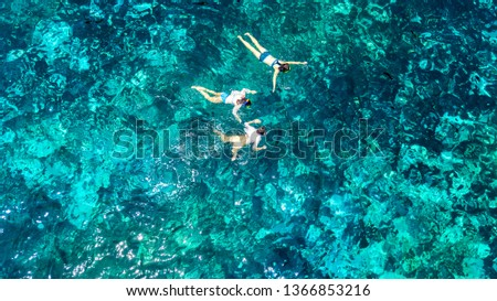 Aerial top view of family snorkeling from above, mother and kids snorkelers swimming in a clear tropical sea water with corals during summer vacation in Thailand #1366853216