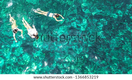 Aerial top view of family snorkeling from above, mother and kids snorkelers swimming in a clear tropical sea water with corals during summer vacation in Thailand #1366853219