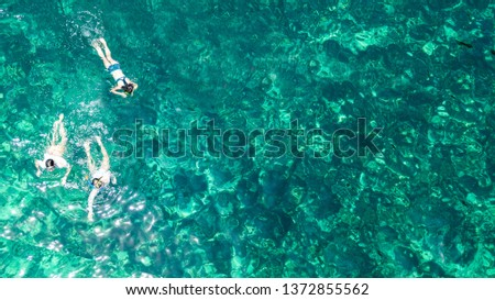 Aerial top view of family snorkeling from above, mother and kids snorkelers swimming in a clear tropical sea water with corals during summer vacation in Thailand #1372855562