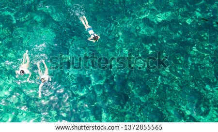 Aerial top view of family snorkeling from above, mother and kids snorkelers swimming in a clear tropical sea water with corals during summer vacation in Thailand #1372855565