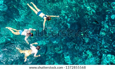 Aerial top view of family snorkeling from above, mother and kids snorkelers swimming in a clear tropical sea water with corals during summer vacation in Thailand #1372855568