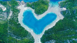 Aerial top view of Love Lagoon Karwapop with turquoise water in heart shape inside of rocky tropical island on Raja Ampat, Papua, Indonesia.
