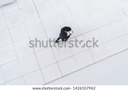Aerial top view of millennial hipster guy using modern digital tablet for online communication via application, male generation walking at urban setting with advertising area using public internet